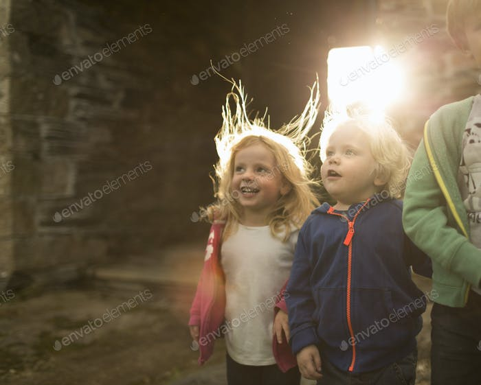 Two children on a farm, looking upwards with curiousity and excitement.