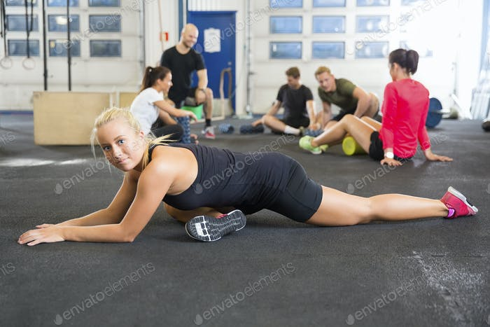 Determined Female Athlete Doing Stretching Exercise At Health Club