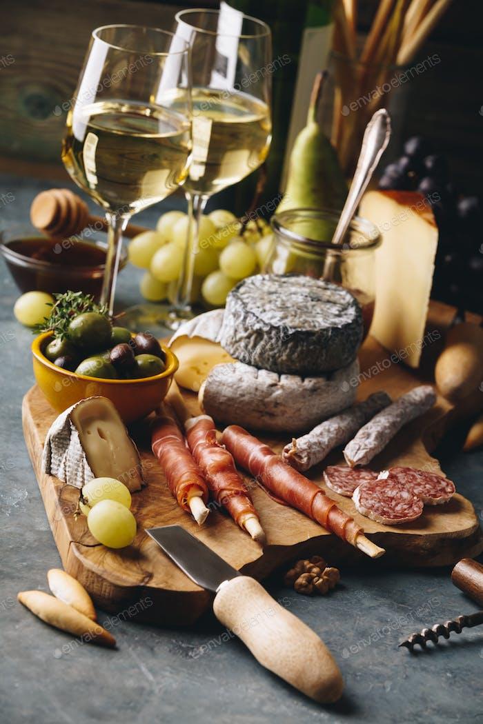 Weißwein mit Wurstsortiment auf dem Steinhintergrund