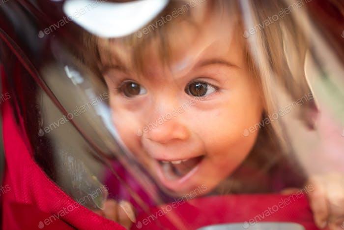 Portrait of baby girl looking through back window of her stroller.