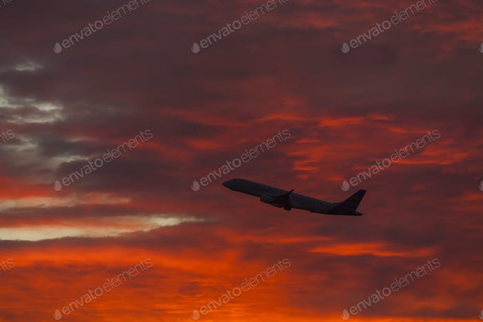 Flying plane on the background of a colorful sunset sky.