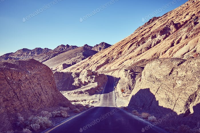 Vintage toned picture of a desert road, USA.