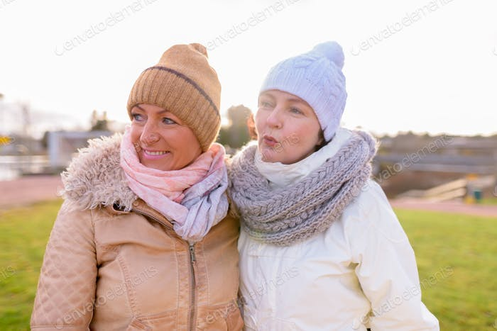Two mature beautiful women together against scenic view of natur