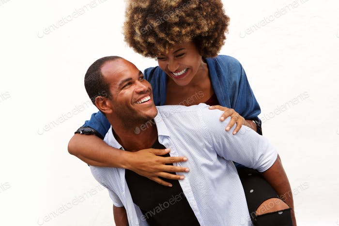 Spaß paar lächelnd in Umarmung durch weiße Wand