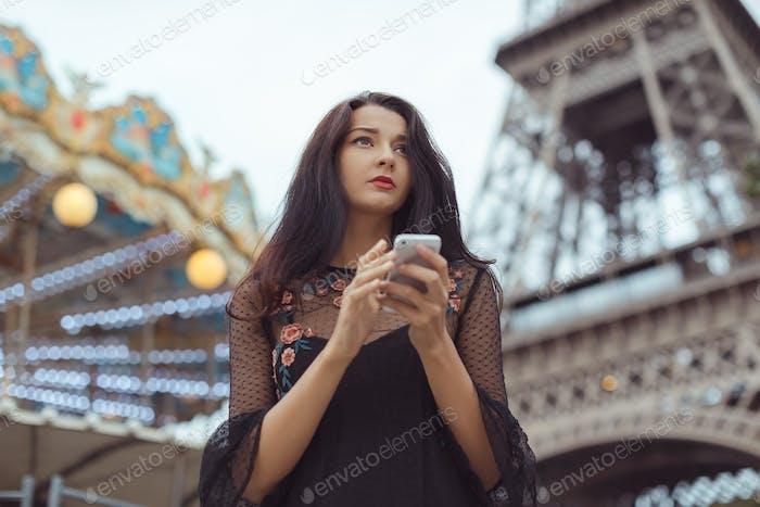 Sad woman using smartphone near the Eiffel tower and carousel, Paris