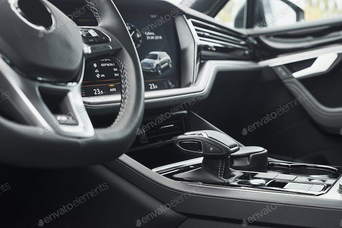 Интерьер престижного современного черного автомобиля. Кожаные удобные сиденья и аксессуары и рулевое управление