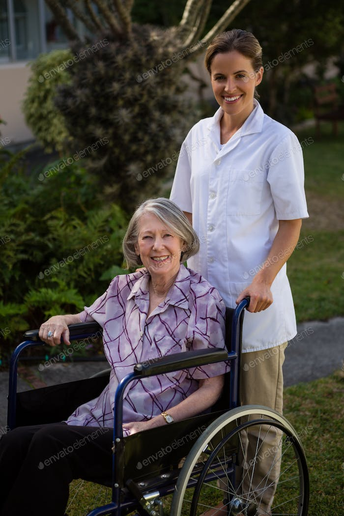 Smiling doctor standing by senior woman sitting on wheelchair in park