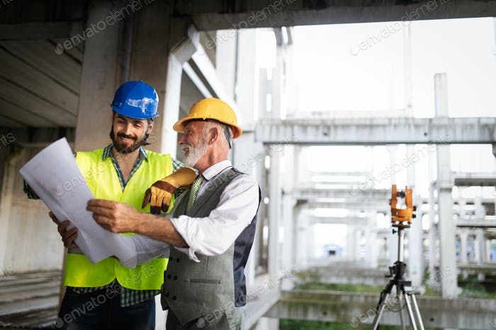 Engineer and building site manager dealing with blueprints and plans