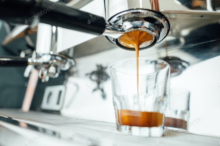 finish of the espresso extraction process from bottomless portafilter in a glass cup,