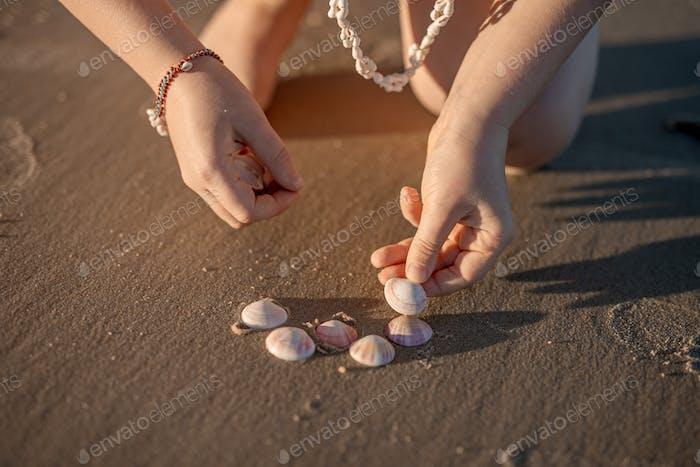 Little girl's hands creating a heart from seashells on the ocean sandy beach.