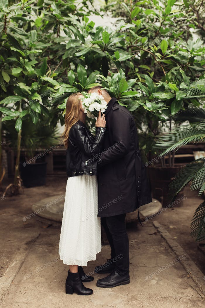 Young attractive couple covering faces with little bouquet of wh