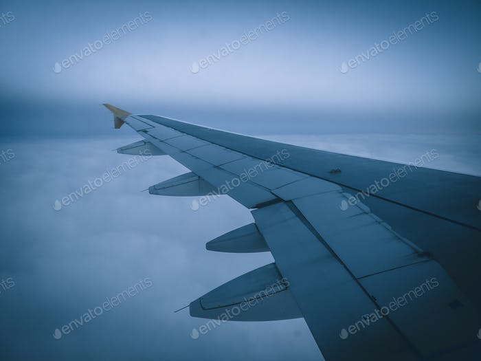 Image of airplane wing flying in bad weather conditions, fog and clouds