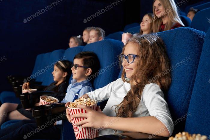 Kids watching movie in cinema, holding popcorn buckets