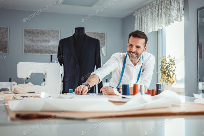 Владелец портного магазина над рабочим столом, ремесленник в швейной мастерской