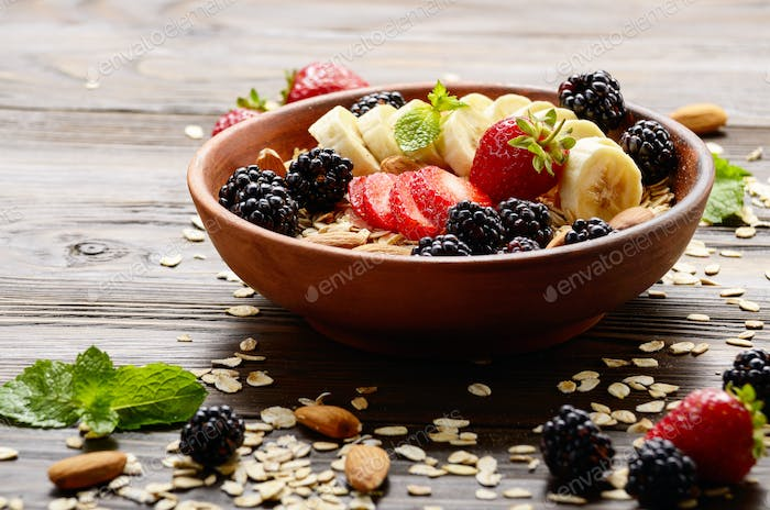 Fruit healthy muesli with banana strawberry almonds and blackberry