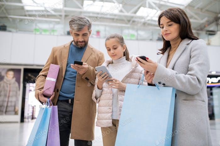 Drei zeitgenössische Shopaholics mit Smartphones, die durch Onlineshops scrollen