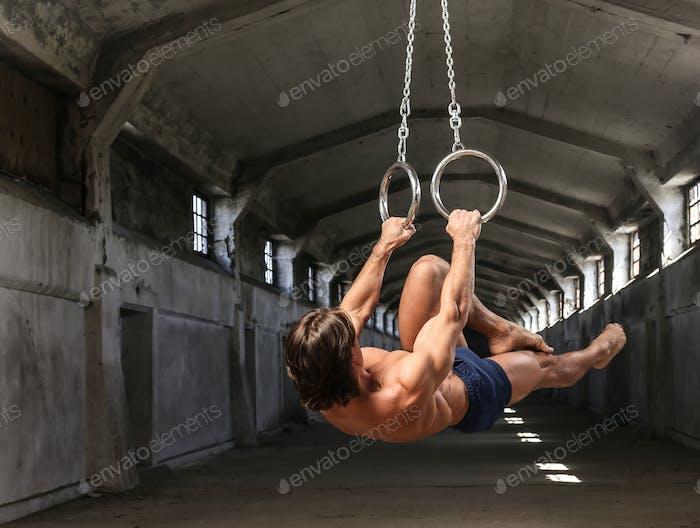 Sportler mit einem schönen muskulösen Körper trainiert auf Gymnastikringen im verlassenen Industriegebäude