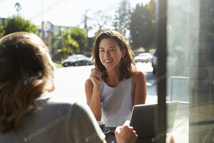 Two female friends using a laptop talking outside a cafe