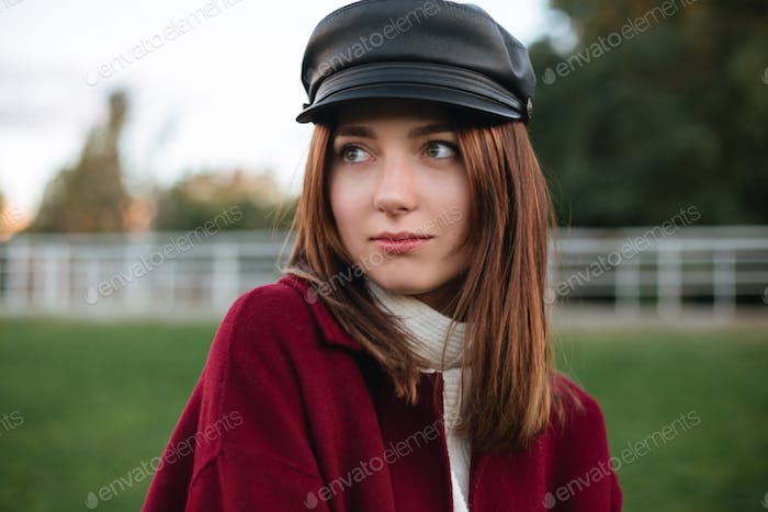 Nice lady in black cap and coat standing in park and thoughtfully looking aside