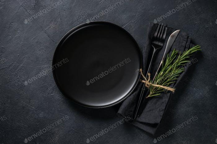 Weißer Teller, Besteck und Serviette auf schwarzem Tisch Ansicht