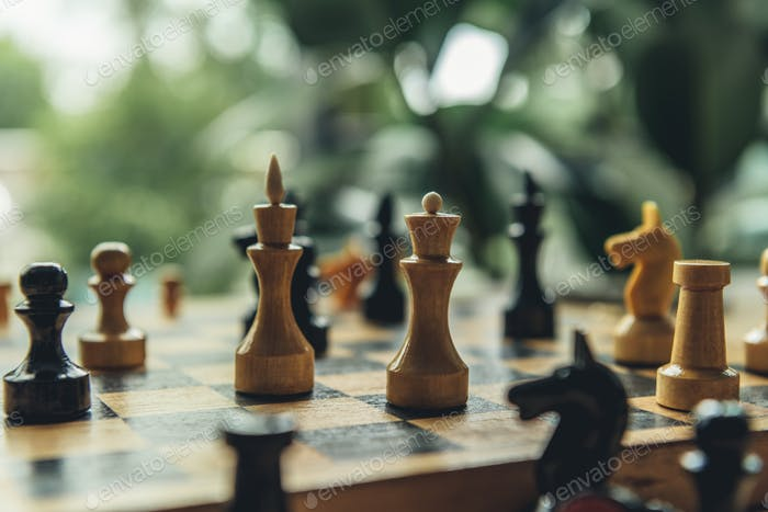 Closeup view of black and white chess figures on chess board. Focus on foreground with white king