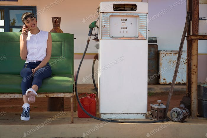 Woman talking on mobile phone at petrol pump station