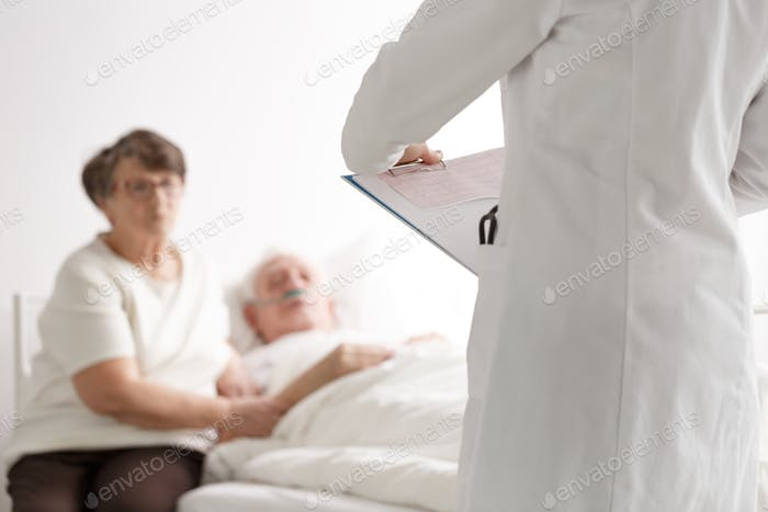 Elderly couple talking with doctor