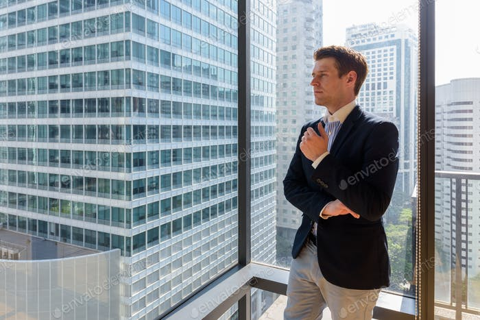 Young handsome businessman standing against glass window in city