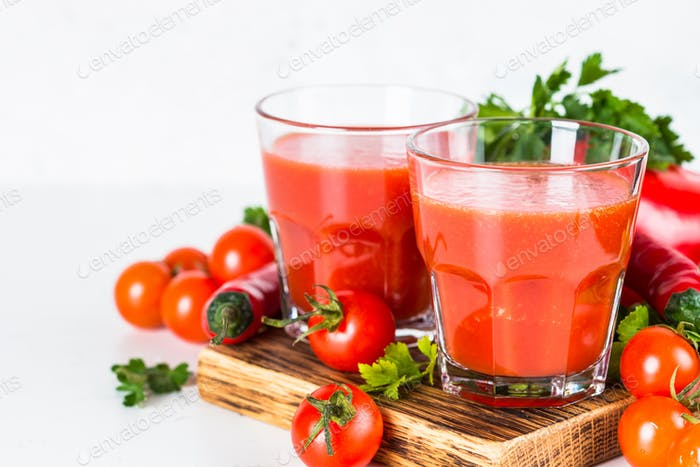 Tomato juice in glass on white