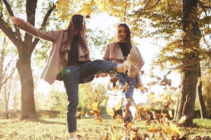 Blick von unten auf junge lächelnde brünette Zwillingsmädchen, die Spaß haben und mit den Füßen Laub treten