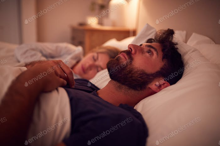 Couple With Man Lying In Bed Awake At Night Suffering With Insomnia