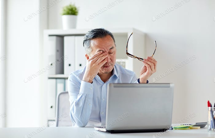tired businessman with glasses at laptop in office