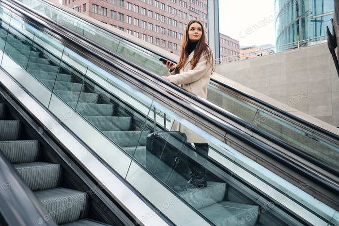 Young beautiful casual businesswoman with suitcase on escalator outdoor