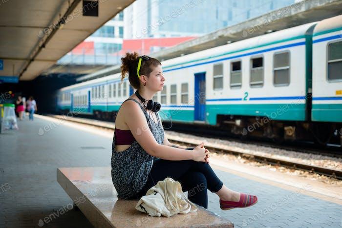 beautiful stylish modern young woman waiting train