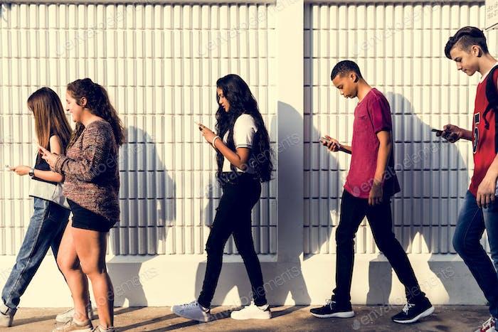 Gruppe von jungen Teenager-Freunden zu Fuß nach der Schule mit Smartphones Sucht Konzept