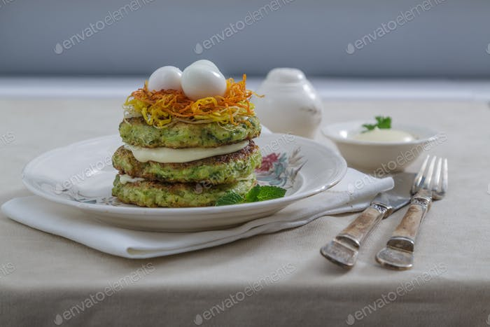 Courgette pancakes with eggs and carrots ot top, copy space