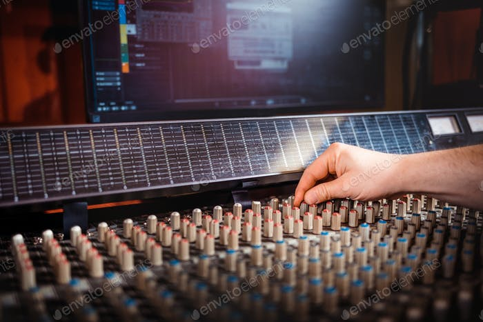 Sound producer working at recording studio using soundboard and monitors