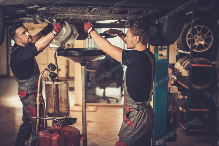 Professional car  mechanic changing motor oil in automobile engi