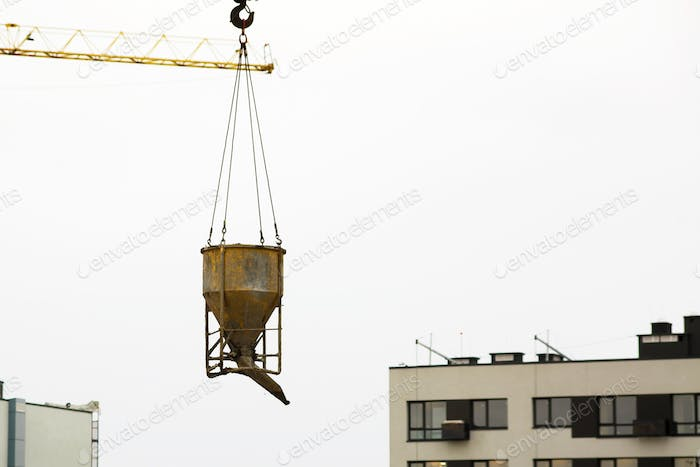 Crane lifting bucket of cement and transporting at construction site at new building skyscrapers