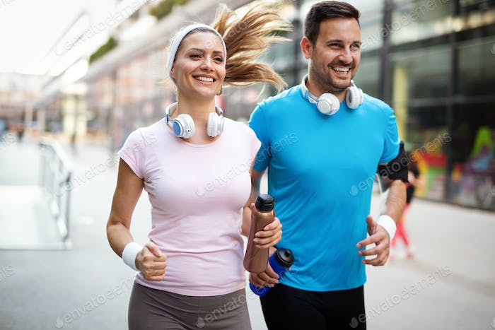 Young people running outdoors. Couple or friends of runners exercising