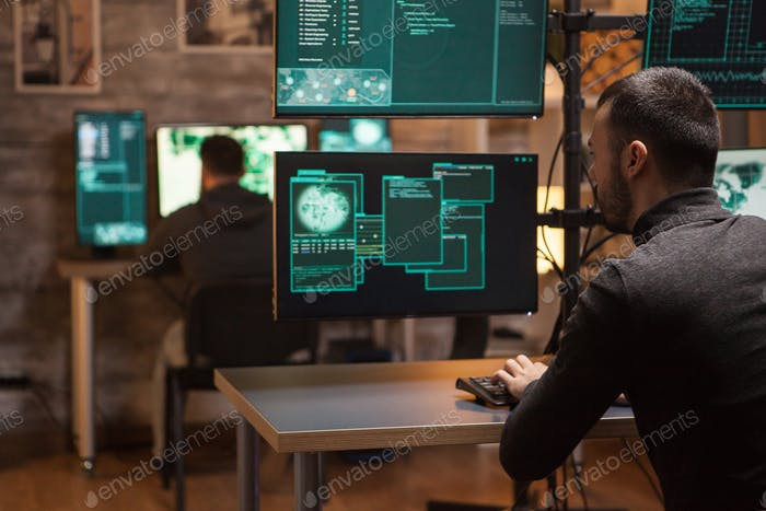 Back view of hackers working on making a dangerous malware