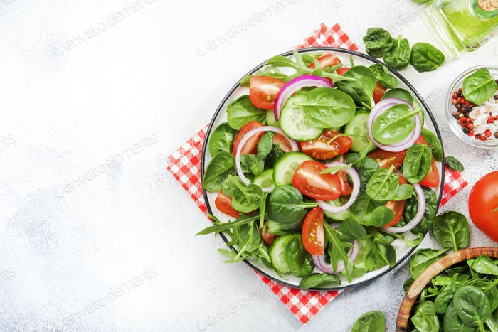 Spring vegan salad with spinach, cherry tomatoes, corn salad
