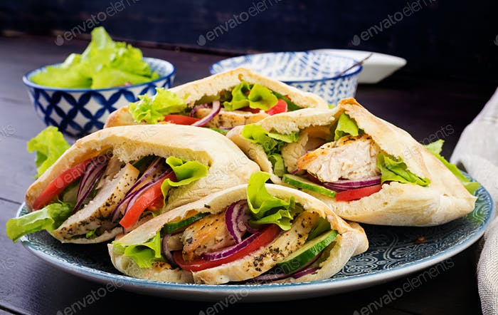 Pita stuffed with chicken, tomato and lettuce on wooden background. Middle Eastern cuisine.