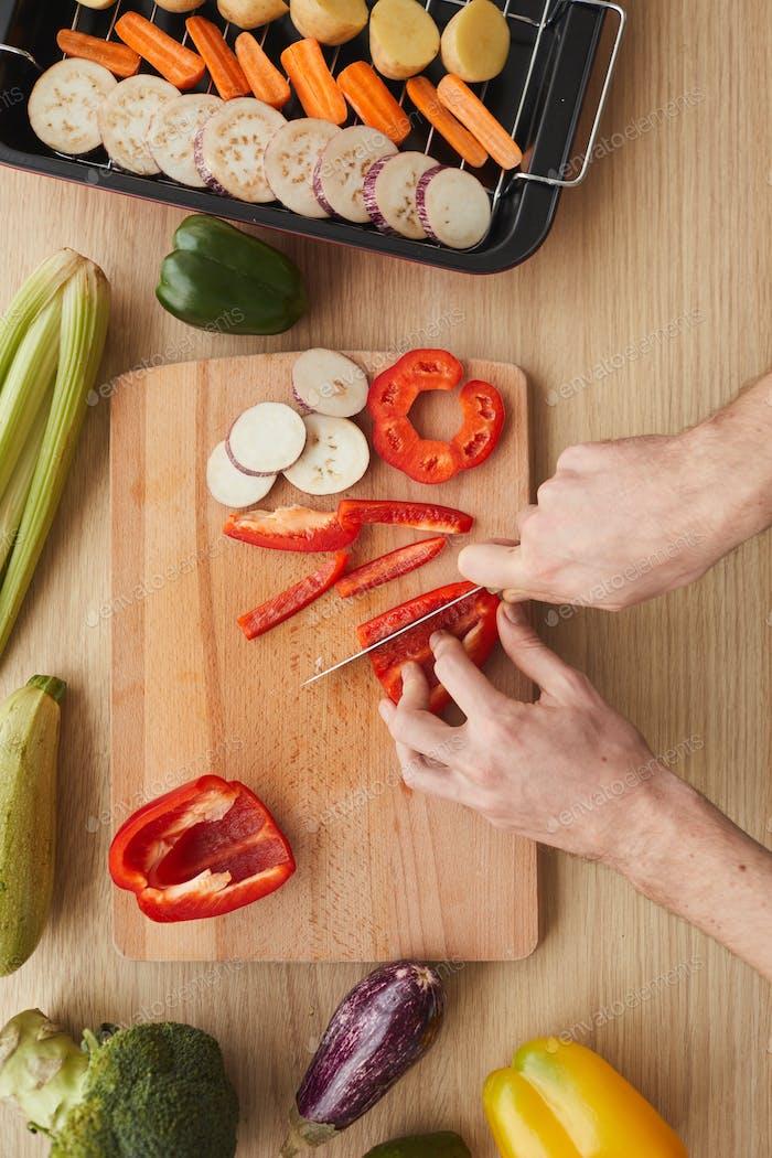 Hombre cortar verduras en tabla de cortar