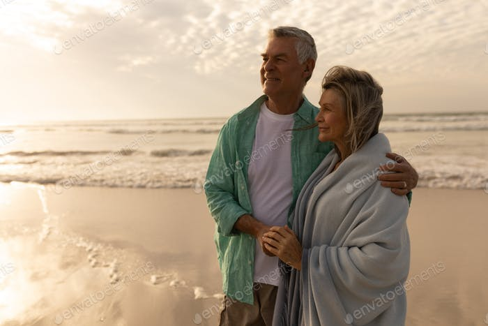 Side view of a thoughtful senior couple embracing each other on the beach