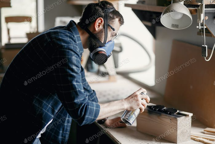 Man holding paint spray and painting wood