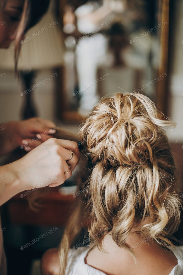 Beautiful happy bride getting her hair done by professional hair stylist