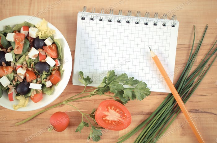 Vintage photo, greek salad with vegetables and notepad for notes, healthy nutrition