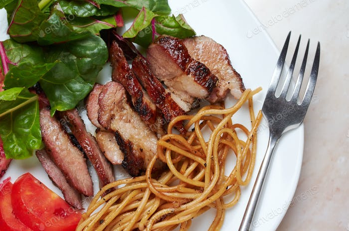 Sliced BBQ pork belly with pasta and salad