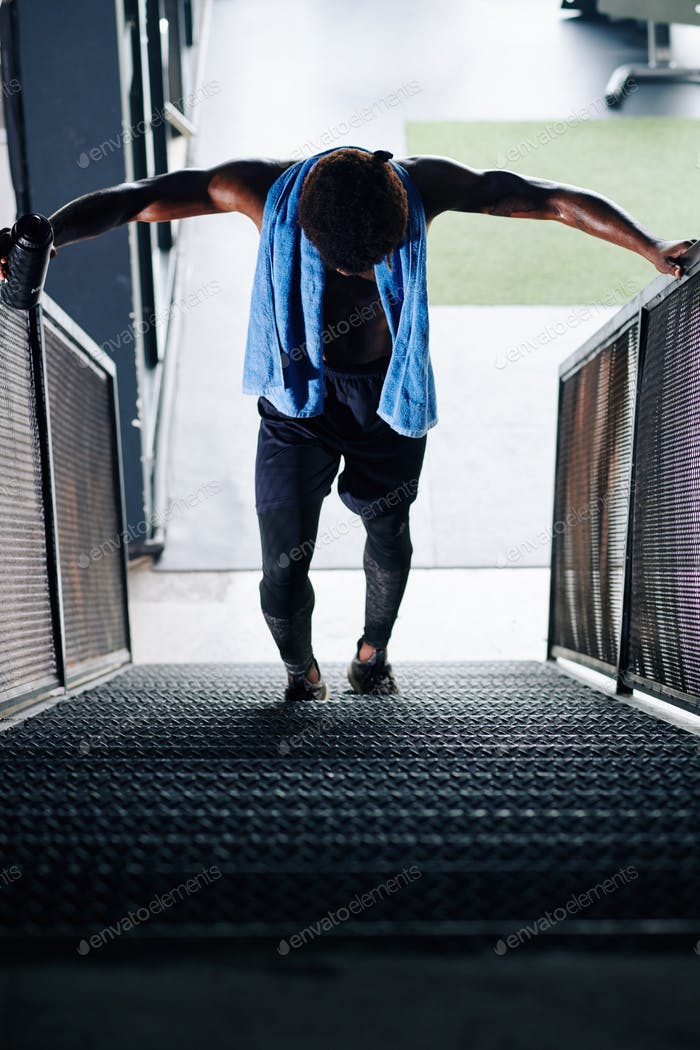 Sportsman struggling walking up the stairs after leg day